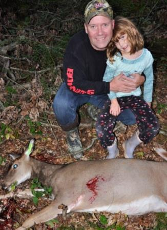 Father and daughter pose next to a doe used for family food