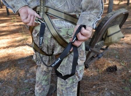A hunter snaps his fall recovery strap into place before climbing his treestand
