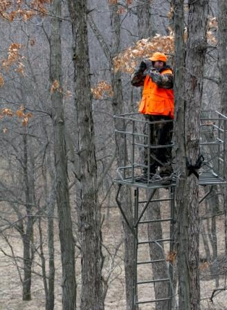 A deer hunter scouting in a treestand