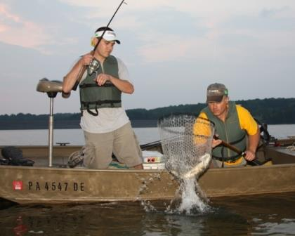 Two anglers netting a fish together