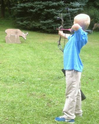 A boy with his bow and arrow shooting a deer decoy