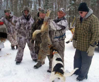 Hunters and a hound gather around a coyote kill