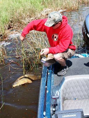 bowfishing, dawson examines his catch
