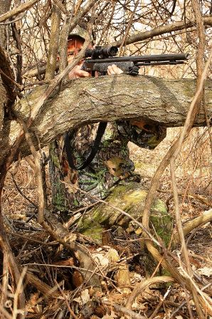 hunter-positioned-inside-tree-brancehs-298x448