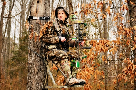 vikki trout in treestand with bow 448x298